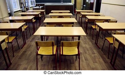 Chairs and tables inside empty physics school class,...