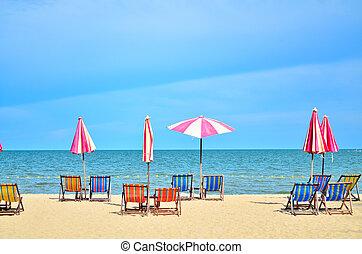 Chairs and umbellar on white sand beach.