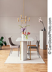 Chairs at table with flowers in modern dining room interior with gold lamp and carpet. Real photo