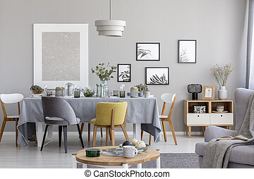 Chairs at table with grey cloth in modern dining room interior with posters and lamp. Real photo
