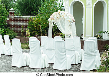 Chairs covered with white cloth stand in the front of wedding altar