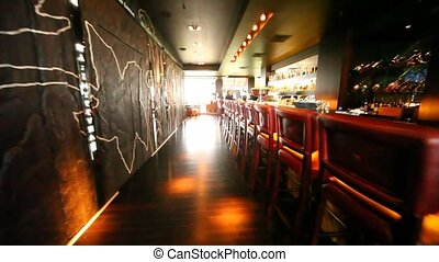 Chairs in bar stand along long bar counter where there are two women working in restaurant