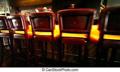 Chairs in bar stand along long bar counter, flying motion