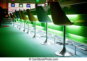 Chairs in bar with green lights - Chairs in row in bar with ...