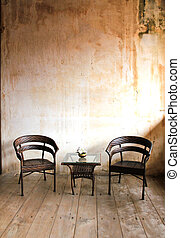 Chairs in front of an old wall