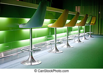 Chairs in row with green lights - Chairs in row in bar with...