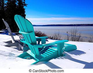 Two adirondack chairs in snow at water's edge; Mahone Bay, Nova Scotia, Canada.