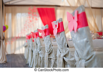 chairs in white covers with a red ribbon
