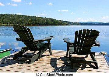 Chairs on dock - Two adirondack wooden chairs on dock facing...