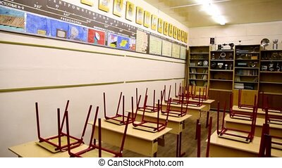 Chairs on tables inside empty physics school class,...