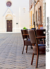 chairs on the narrow street in old town