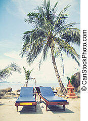 chairs on tropical beach with palm tree (Vintage filter effect used)