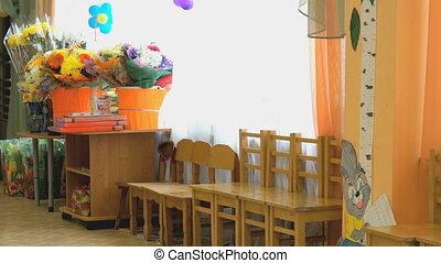 Chairs, table, flowers. Interior of kindergarten