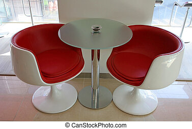 Two modern red chairs and a table