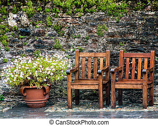 Chairs  - Two wooden chairs sitting next to flowers