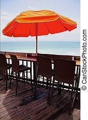 Chairs under an umbrella on a pier