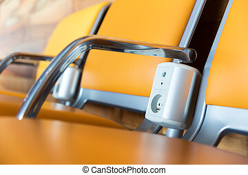 Chairs with electric outlet in airport.