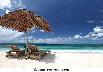 Chairs with parasol on beach - Relaxing couch chairs with...