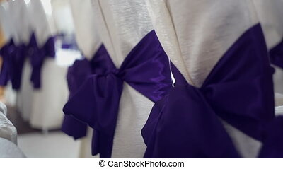Chairs with purple bows for the wedding ceremony