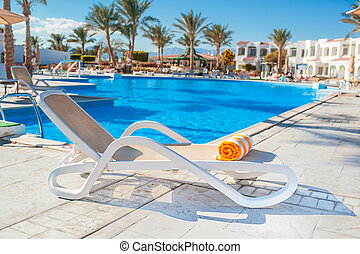 chaise longue on the background of the pool at the hotel