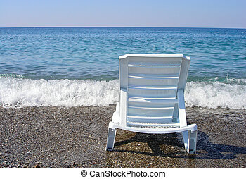 chaise-longue stands on sandy beach