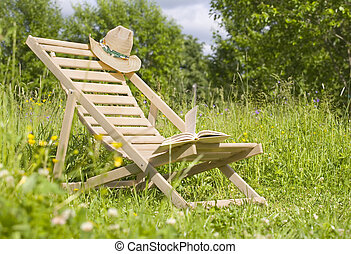 Chaise-longue with a hat and a book in the meadow