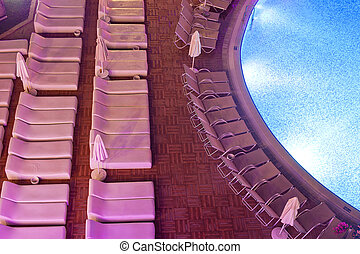Chaise-longues by the pool in the evening