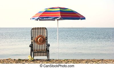 Chaise lounge deck chair and umbrella. Early morning on the...