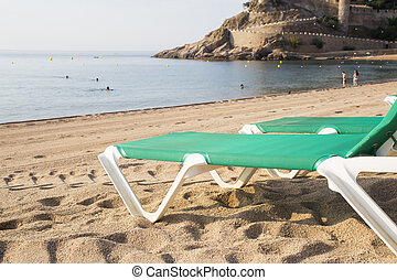 Chaise-Loungers on deserted beach in Tossa De Mar, Spain.