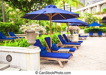 Chaise lounges near pool in luxury resort