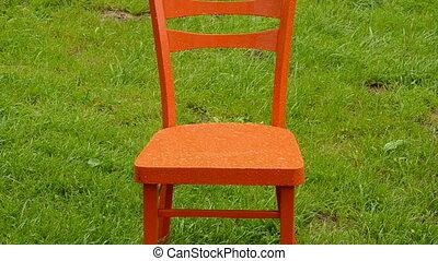 chaise orange, herbe, pluie