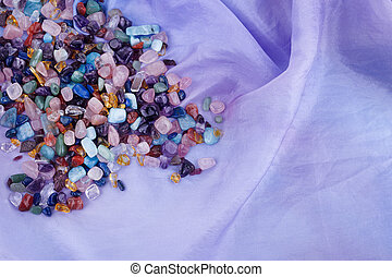 chakra healing crystals on pastel silk background