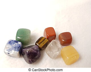 Chakra stones - natural cubic gems on a white background: jasper, tiger's eye, charoite, lapis lazuli, agate, amethyst, quartz. Stock photo horizontal with copy space, suitable for banner, advertising booklet