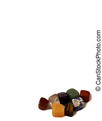 Chakra stones - natural cubic gems on a white background: jasper, tiger's eye, charoite, lapis lazuli, agate, amethyst, quartz. Stock photo vertical with copy space, suitable for banner, advertising booklet