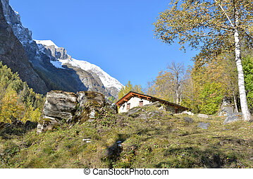 chalet  in alpine mountain landscape with snowy mountain background under blue sky