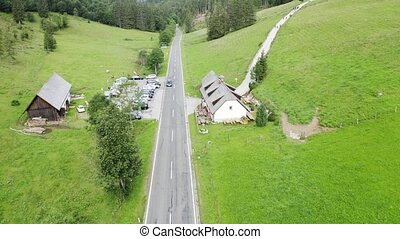 Aerial view mountain and forest landscape of alps with chalet and road