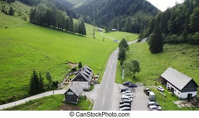 Aerial view mountain and forest landscape of alps with chalet cabin and road