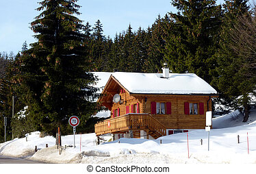 Brown chalet in Jura mountain with fir trees behind in Switzerland by winter