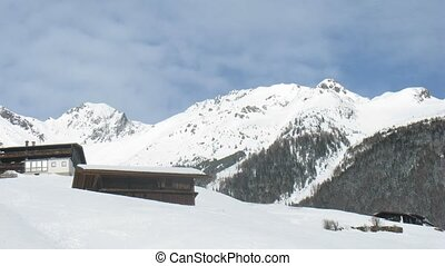 Chalets stand on slope of mountain against mountains and are...