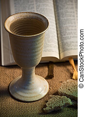 Chalice of wine, open bible and bread