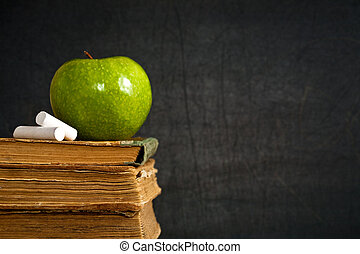 Chalk and green apple on old textbook against blackboard in class. School concept