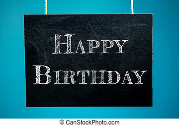 "Chalk board is hanging with the inscription ""Happy Birthday"" on a blue background. copy space"
