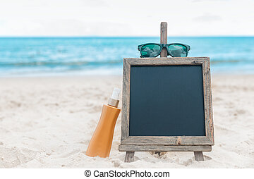 Chalk board with sunscreen cream in the sand on the beach...