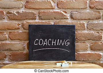 Chalk board with the word COACHING drown by hand on wooden table on brick wall background.