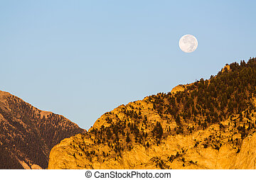 Valley by chalk white cliffs of Mount Princeton near Buena Vista in Colorado as setting moon drops over horizon at sunrise