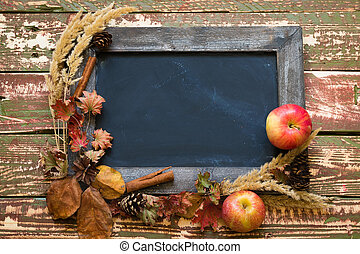 Chalkboard in the frame of dried flowers and apples