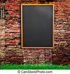 Chalkboard on Old brick wall and green grass
