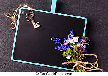 Chalkboard with flowers and key
