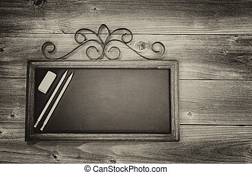 Vintage concept of an old fashion chalkboard, pencils and eraser on rustic wood. Layout in horizontal format.
