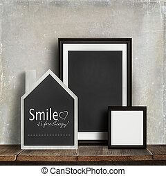 Chalkboard with quote and frames on table